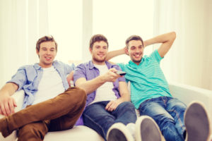 three men sit on a couch with their feet one, one raises a TV remote