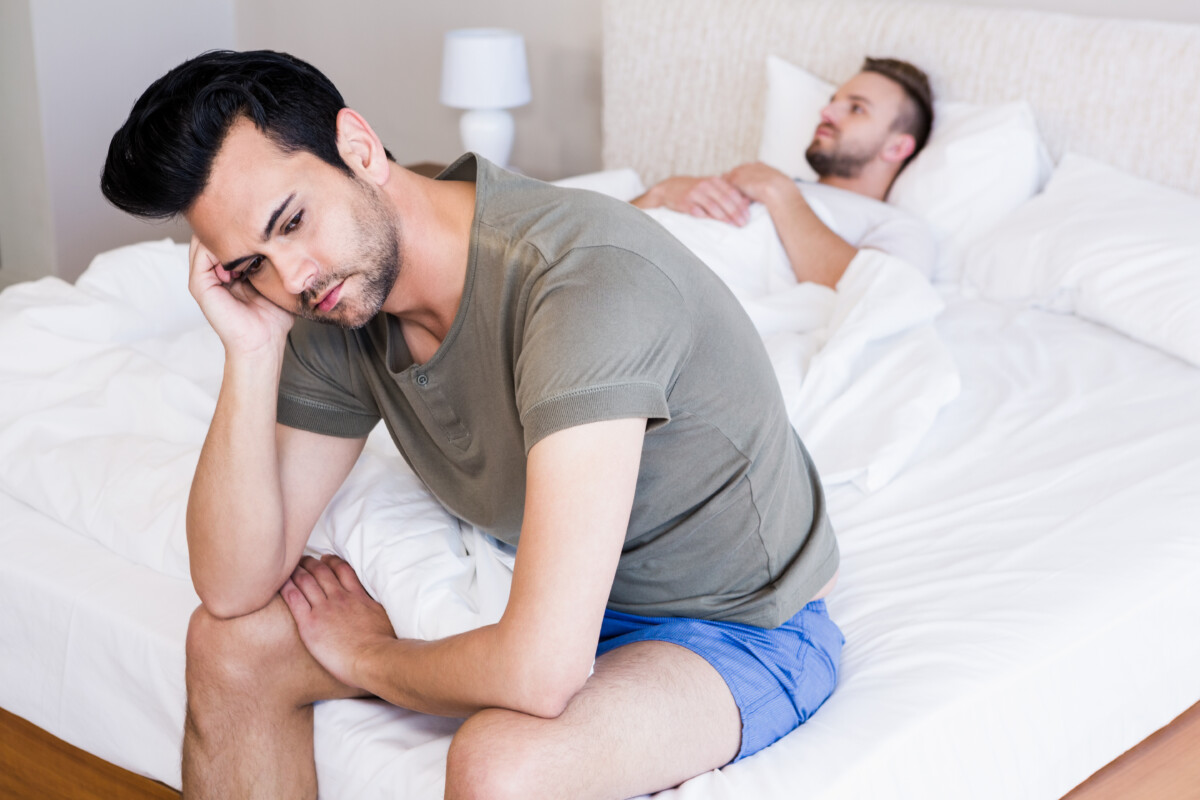 2 gay men in bed with one sitting on the edge looking frustrated