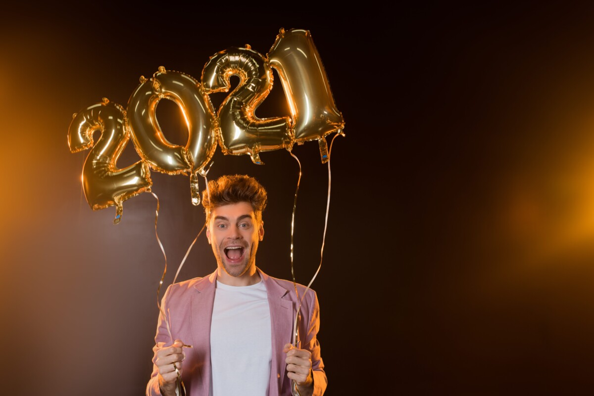 man holding 2021 balloon