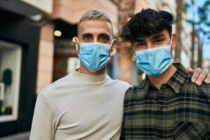 young gay couple wearing masks