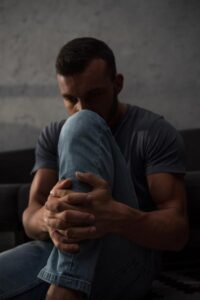 distressed looking man sitting on the floor hugging his knee with face partially obscured by knee